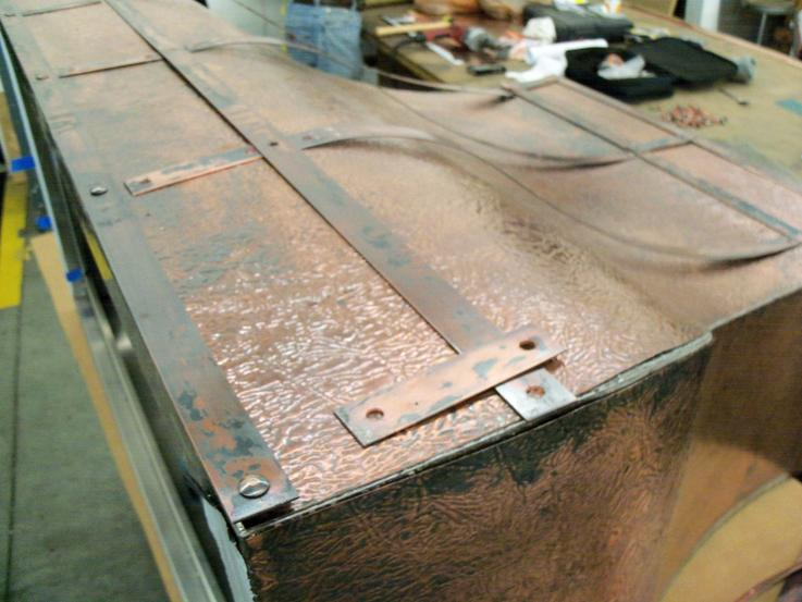 Preparing copper luggage straps to be attached to the body of the hood.